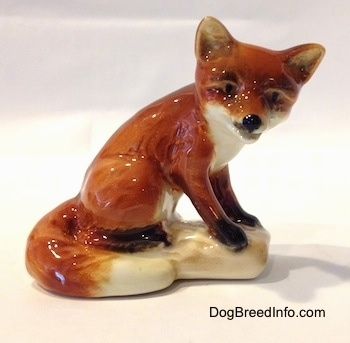 The right side of a porcelain red fox figurine sitting on a log. The figurine has black circles for eyes and a black nose.
