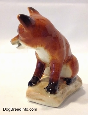 The front left side of a red fox porcelain figurine that is sitting on a log. The figurine has a white chest and the back of its ears are black.