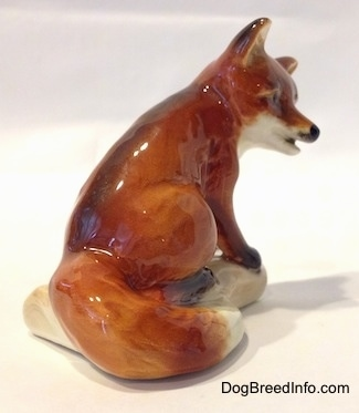 The back right side of a porcelain figurine of a red fox. The figurine has its mouth slightly open and its tail is around a log.