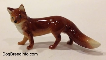 The left side of a red fox figurine. The figurine has black circles for eyes and it has a black circle for a nose.