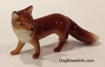 The front left side of a red fox figurine. The figurine has a white chest.