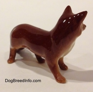 The front right side of a figurine of a red fox. The back of the figurine is glossy.