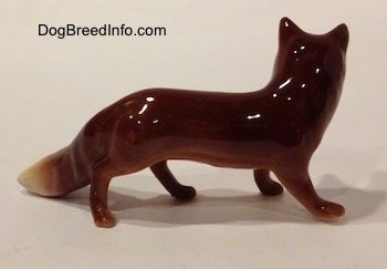 The right side of a red fox figurine. The figurine has a glossy finish.