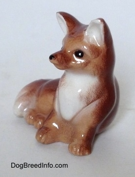 The front left side of a baby Fox seated figurine. The Fox has a white chest and a white tipped tail.