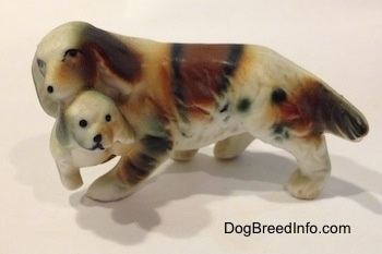 The left side of a brown and white with black bone china of a French Brittany Spaniel carrying a puppy. Both parts of the figurine have black circles for eyes.