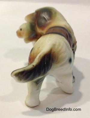 The back of a brown and white with black bone china of a French Brittany Spaniel carrying a puppy. The figurine has a long tail.
