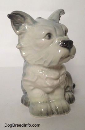A white with black French Bull Tzu figurine is in a sitting pose. The figurine has fine chest details.
