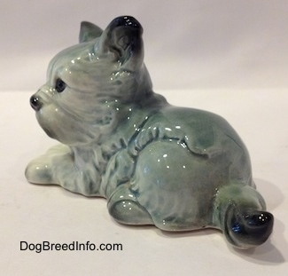 The back left side of a figurine of a white with black French Bull Tzu in a laying down pose figurine. The figurine has a black tipped tail.