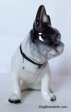 A white and black figurine of a French Bulldog in a sitting pose. The figurine has black tipped nails.