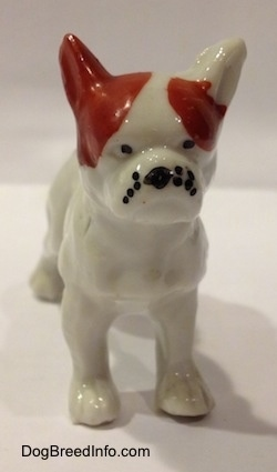 A white with red bone china French Bulldog figurine that has black circles for eyes.