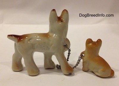 The left side of a brown with white and black French Bulldog that has the word - JAPAN - engraved on it. The figurine is also chained to a figurine of a brown with tan Frenchie puppy.