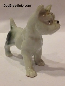 The front right side of a porcelain figurine of a white with brown and green French Bulldog in a standing pose. The figurine has small black circles for eyes.