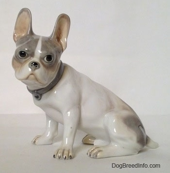 The left side of a white with grey French Bulldog. The Bulldog figurine has a detailed face and large standing ears.