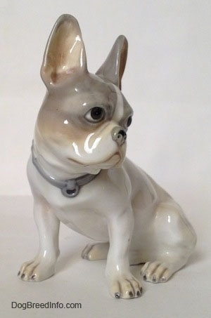 A figurine of a white with grey French Bulldog that has white paws with black nails.