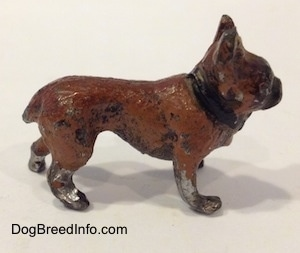 The right side of a brown with black metal French Bulldog figurine. The paint on the legs and body of this figurine are chipped.