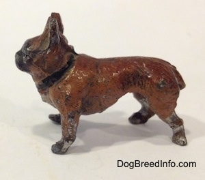 The left side of a brown with black French Bulldog figurine made of metal. The figurine has a short tail and big standing ears.