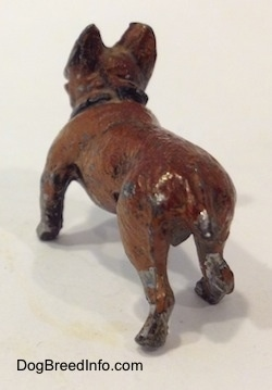 The back left side of a figurine of a brown with black French Bulldog that is made of metal. The figurine has a short tail with chipped paint towards the end.