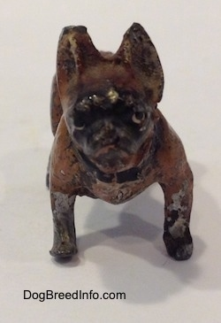 A metal figurine of a brown with black French Bullldog. The figurine has short brown legs and short black paws.