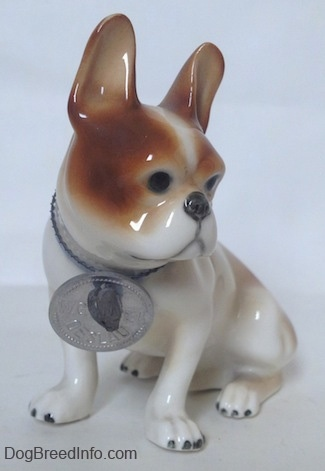A brown and white French Bulldog in a sitting pose figurine. The figurine has large brown ears in the air.