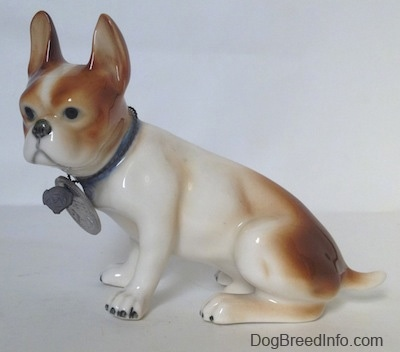 The left side of a brown and white French Bulldog figurine in a sitting pose. The figurine is wearing a blue collar and it has a large medallion on the collar.