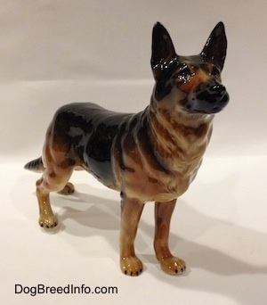 The front right side of a figurine of a black and tan German Shepherd standing. The figurine has detailed black circles for eyes and a black muzzle.