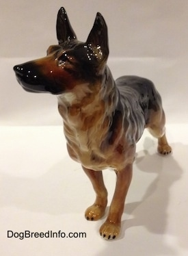 The front left side of a black and tan German Shepherd standing figurine. The figurine has long legs with black tipped nails.