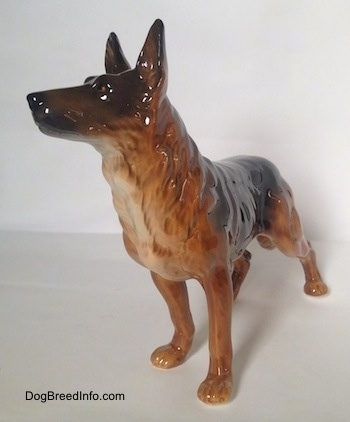 The front left side of a brown with black standing German Shepherd figurine. The figurine has its ears in the air.