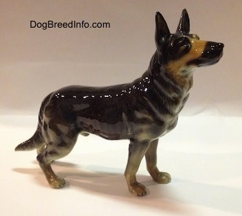 The right side of a black with tan German Shepherd figurine that has fine hair details along its body.