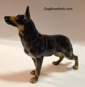 The front left side of a figurine of a black with tan German Shepherd standing figurine. The figurine has its ears alert in the air.