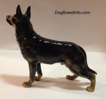 The left side of a black with tan figurine of a standing German Shepherd. The figurine has a glossy side.
