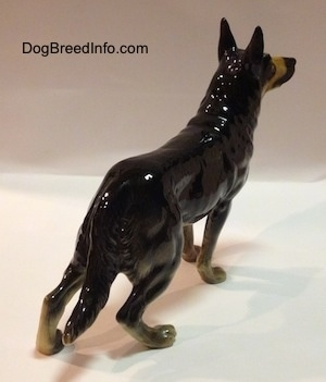 The back right side of a black with tan standing German Shepherd figurine. The figurine has a long fluffy tail.