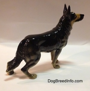A black with tan figurine of a German Shepherds right side. The figurine has long legs.