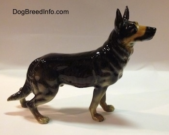 The right side of a figurine of a black with tan German Shepherd standing. The figurine has muscle details in legs.