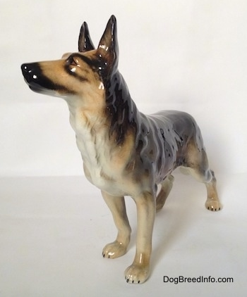 The front left side of a black and grey standing German Shepherd figurine. The figurine has its ears in the air.