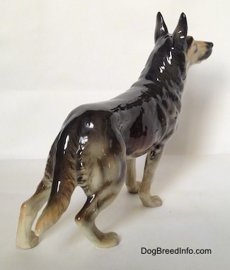 The back right side of a black and grey figurine of a standing German Shepherd.