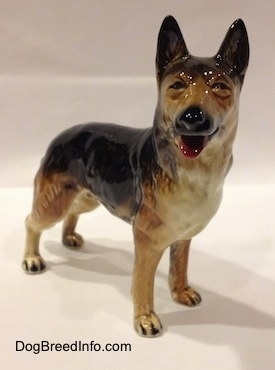 The front right side of a porcelain figurine of a black with brown and white standing German Shepherd. The figurine has squinty eyes.