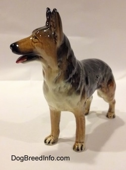 The front left side of a figurine of a porcelain black with brown and white German Shepherd standing. The figurine has its mouth open.