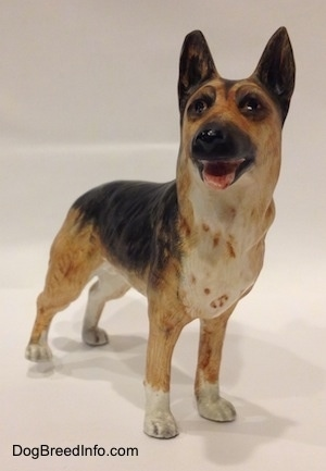 A porcelain figurine of a black and tan with white standing German Shepherd. The figurines mouth is open and tongue is sticking out.