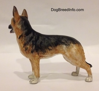 The left side of a porcelain black and tan with white figurine of a German Shepherd standing. The figurine has fine hair details along its body.