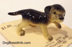 The right side of a black with tan German Shepherd standing puppy figurine. The figurine has black tipped paws.