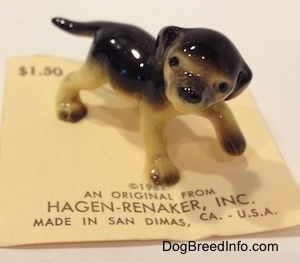 The front right side of a black with tan figurine of a standing German Shepherd puppy. The figurines ears are flopped over and hard to differentiate from its head.