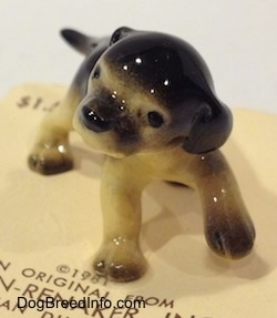 A figurine of a black with tan German Shepherd puppy standing. The puppy has its front left paw in the air.