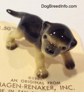 The front left side of a black with tan figurine of a German Shepherd puppy. The figurine has its head tilted and big black circles for eyes.