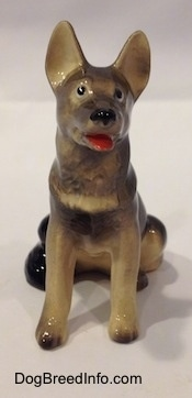 A figurine of a black with grey and tan German Shepherd sitting.