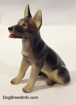 The front left side of a black with tan sitting German Shepherd figurine. The figurine has black circles for eyes with a small white circle inside of it.