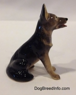 The right side of a black with tan figurine of a German Shepherd sitting. The figurine has its ears in the air.