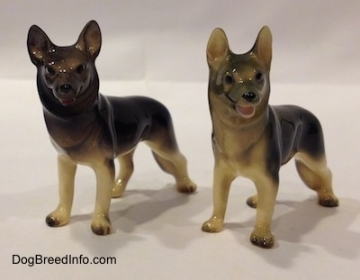 The front left side of two black with tan German Shepherd standing figurines. The figurines have black circles for eyes and a nose.