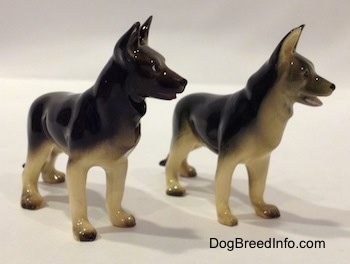 The front right side of two figurines of black with tan German Shepherds standing. The figurines have there mouths open.