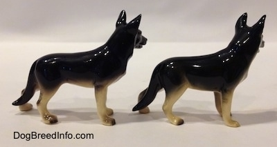 The right side of two black with tan figurine of a German Shepherd standing. The figurines have long legs.