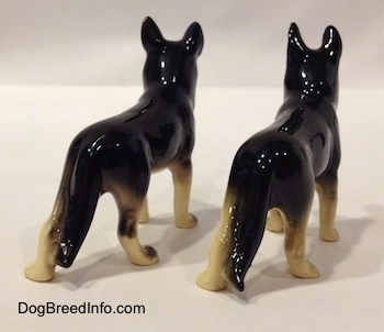The back right side of two black with white figurines of German Shepherds standing. The figurines have glossy backs.